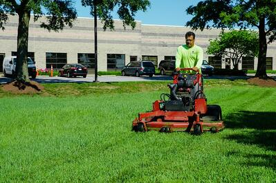 Professional landscaper mowing commercial lawn