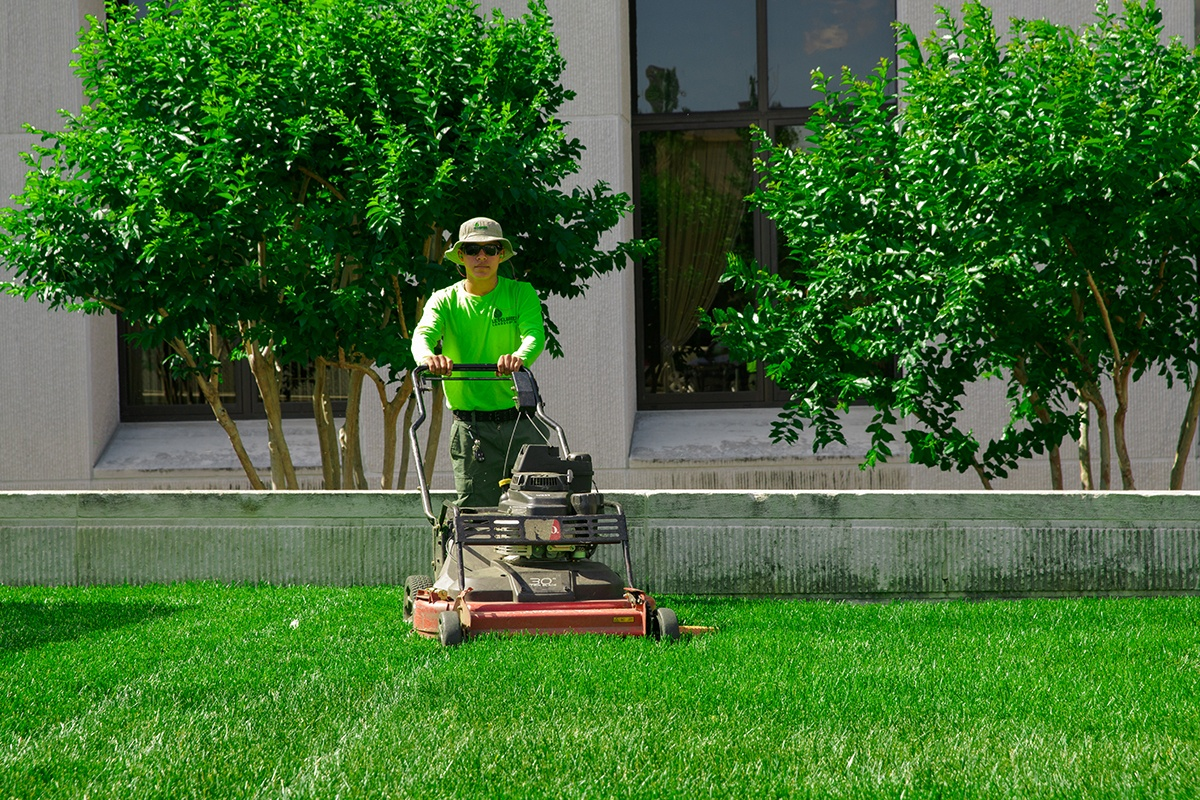 Level Green Landscaping lawn technician in uniform and hat