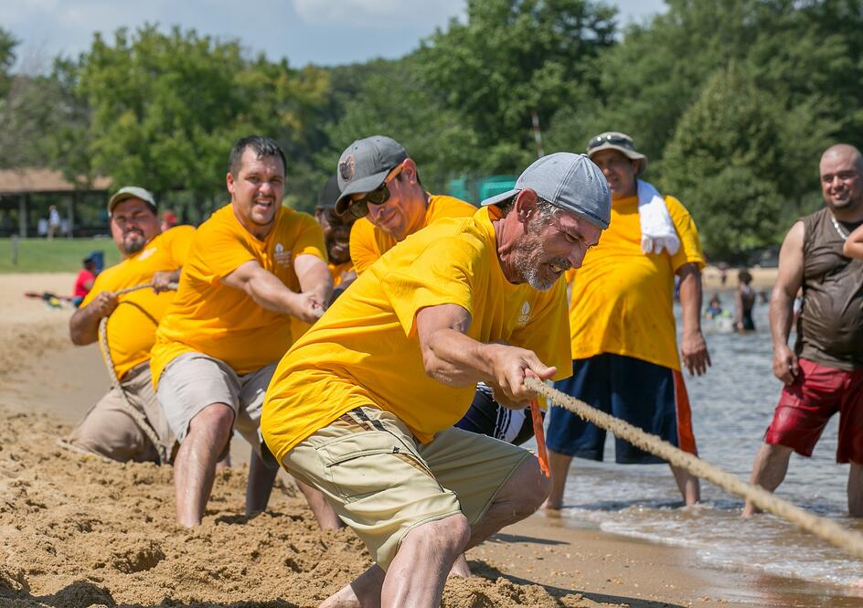 Brad and the yellow team playing tug of war at the company picnic