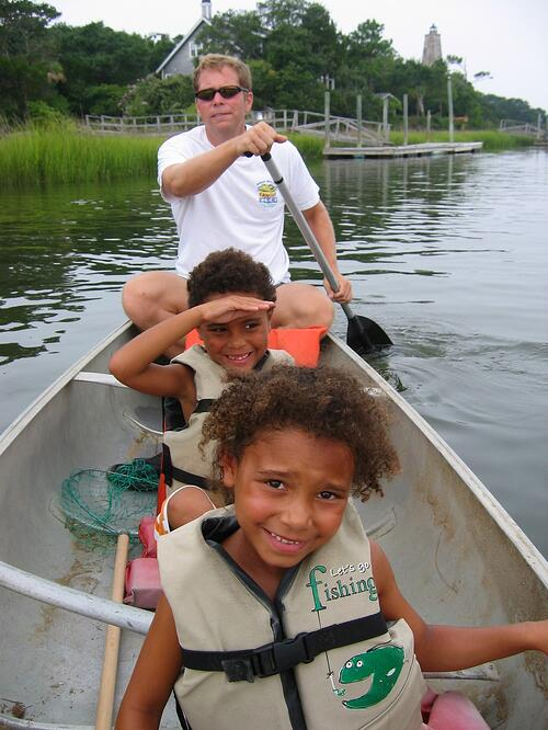 Larry Leon and his children in boat