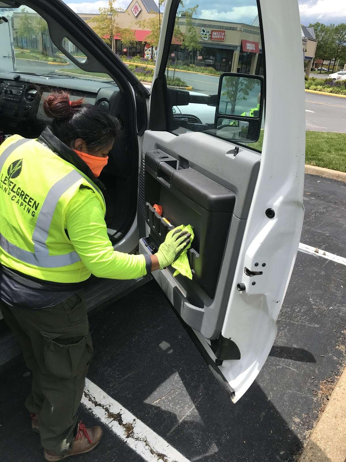 Level Green Landscaping crew member sanitizing truck